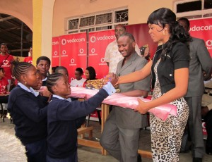 Miss Vodacom Tanzania 2010 Geneviva handing over the fabrics materials to the street children who are studying tailoring course at self help vocational center